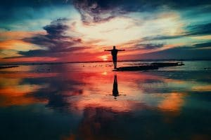 Are You Resurrected? Online Program with Brian J. Plachta | Photo of person with outstretched arms on beach at sunset | Dominican Center, West Michigan